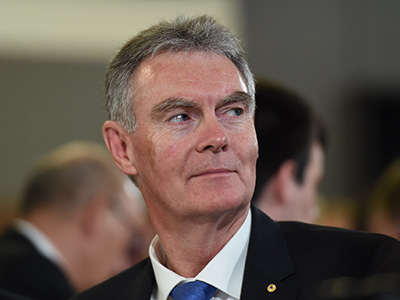The Director General of ASIO, Duncan Lewis, listens to Attorney-General George Brandis addressing the National Press Club in Canberra, Wednesday, Oct. 1, 2014. (AAP Image/Lukas Coch) NO ARCHIVING